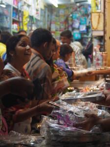 ステンレスの皿など台所用品を買い求める人々